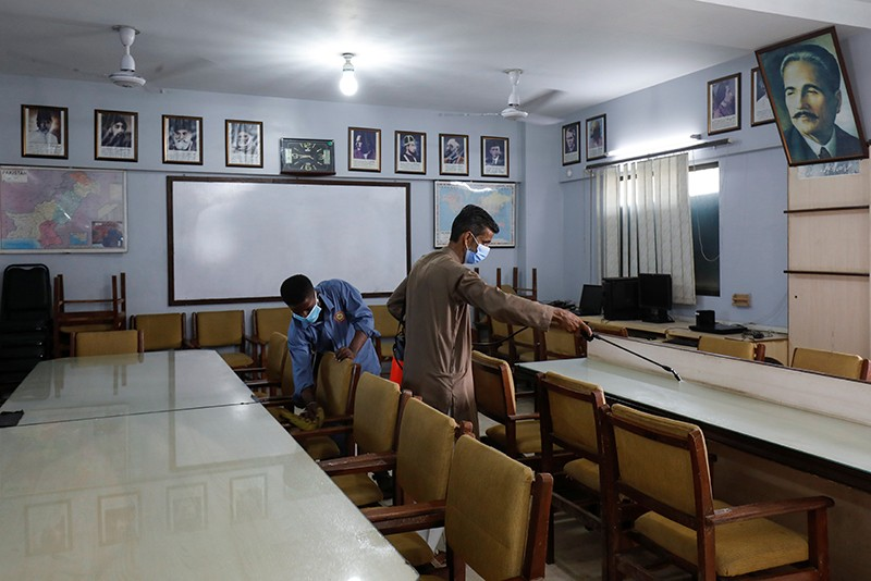 Employees spray sanitizer and clean chairs in the library at a school in Karachi, Pakistan