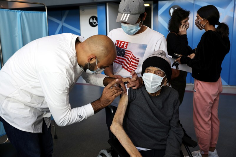An elderly man receives a vaccination against COVID-19 in a vaccination centre in Israel