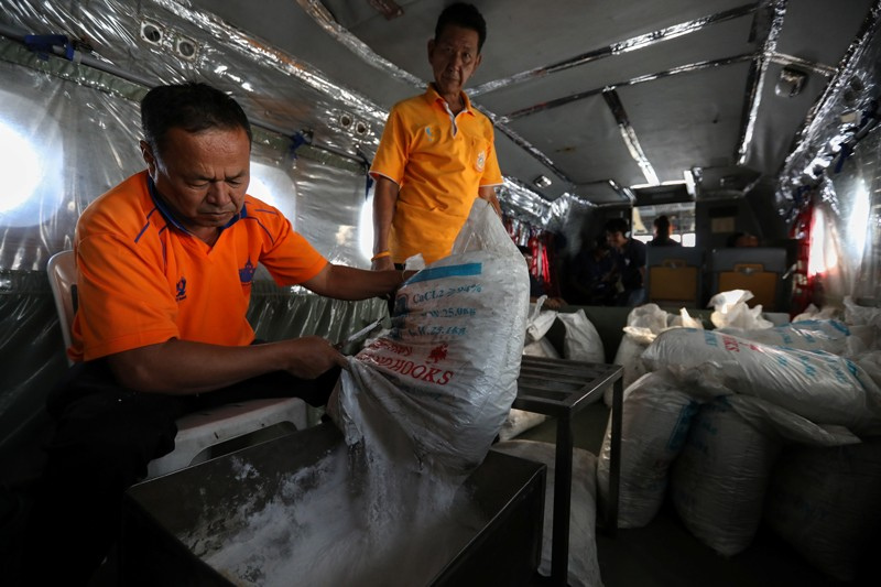 Workers pour chemicals as an aircraft flies over the outskirts of Bangkok
