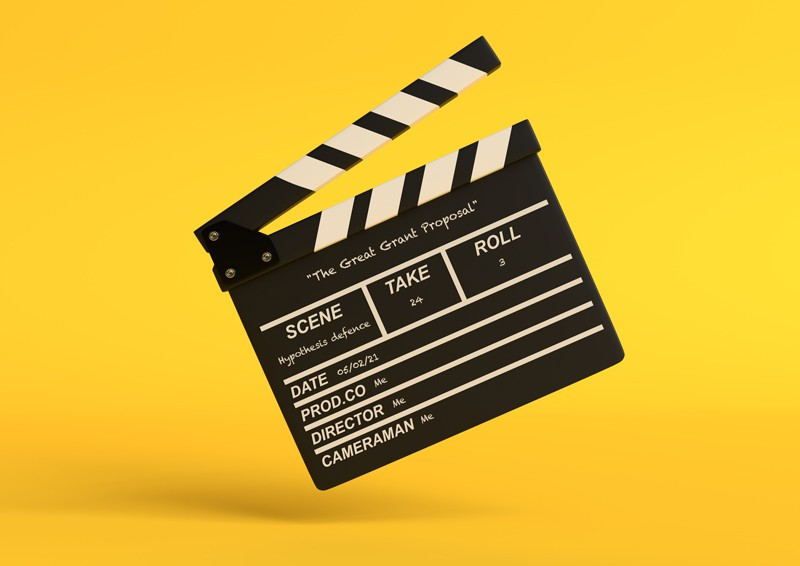 Flying clapperboard isolated on yellow background