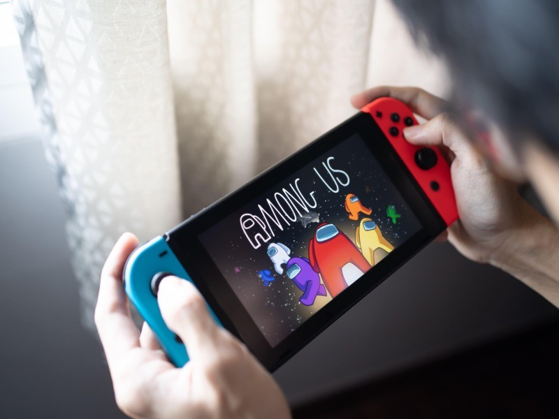 A man playing Among Us, the Best Mobile Game at The Game Awards 2020, on Nintendo Switch.