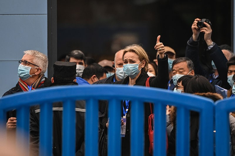 Researchers in face masks cluster behind a blue barrier.
