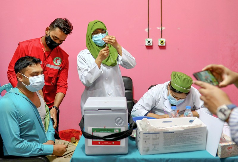 A man sits while medical workers prepare vaccines.