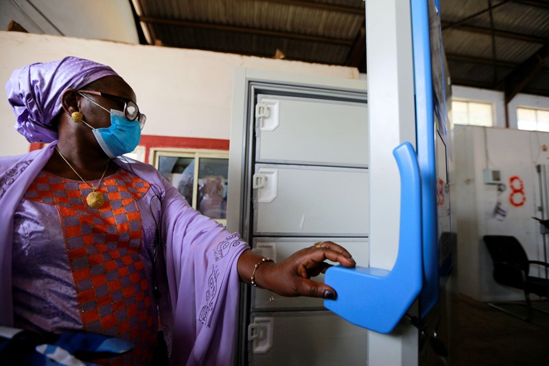 A women in a face mask opens one of the new ultra low temperature freezers at a facility in Nigeria