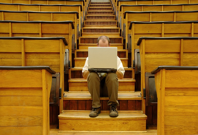 A man sits alone with a laptop in a university hall.