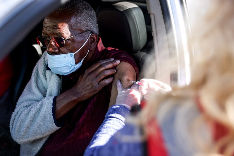 A health0care worker administers a vaccination through a car window to an older man
