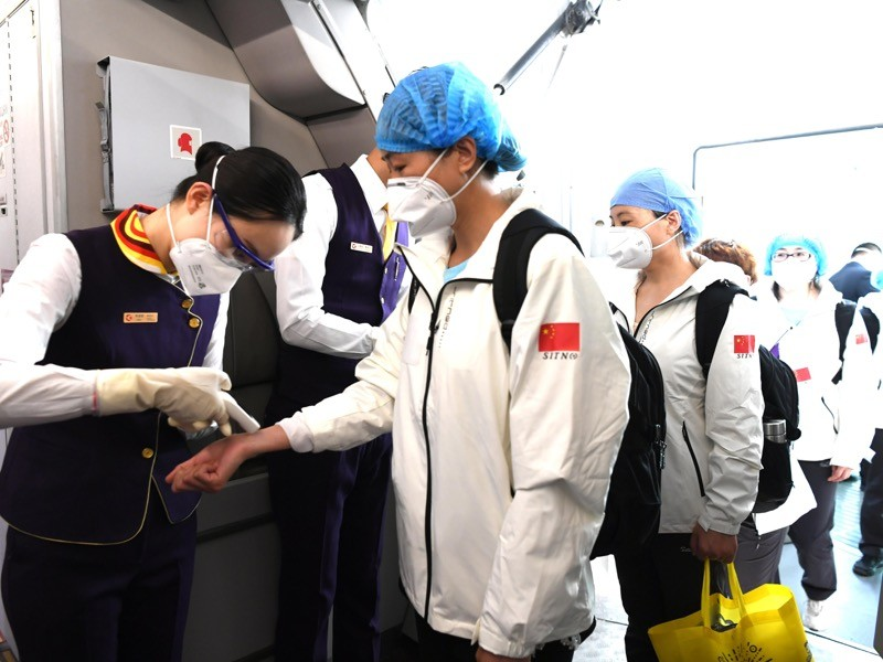 Crew members check temperature of members of a medical assistance team aboard a plane, Wuhan.