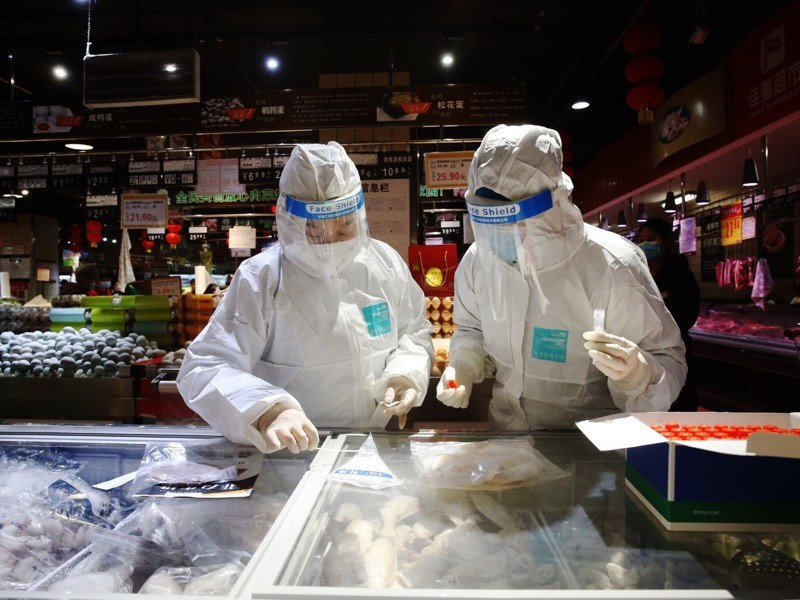 Two people in protective gear and visors swab food in a freezer at a market.