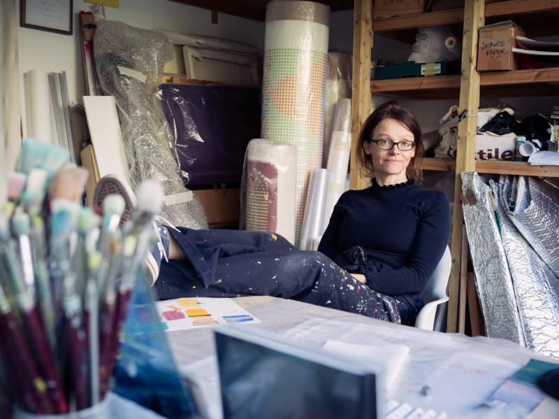 Geraldine Cox poses for a portrait in her artists studio with her feet up on the desk, surrounded by brushes and canvases