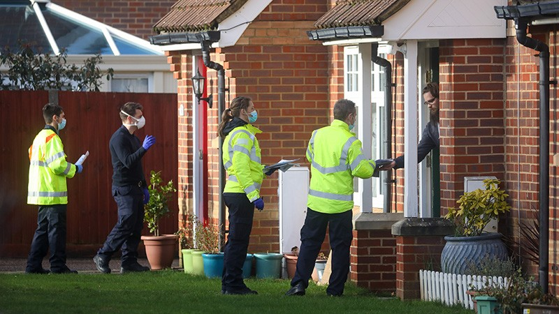 Emergency services workers go door-to-door handing out Covid-19 testing kits in the UK