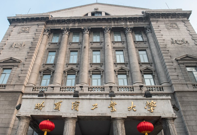 A stone building with columns and porticos, and an entrance sign in Chinese.