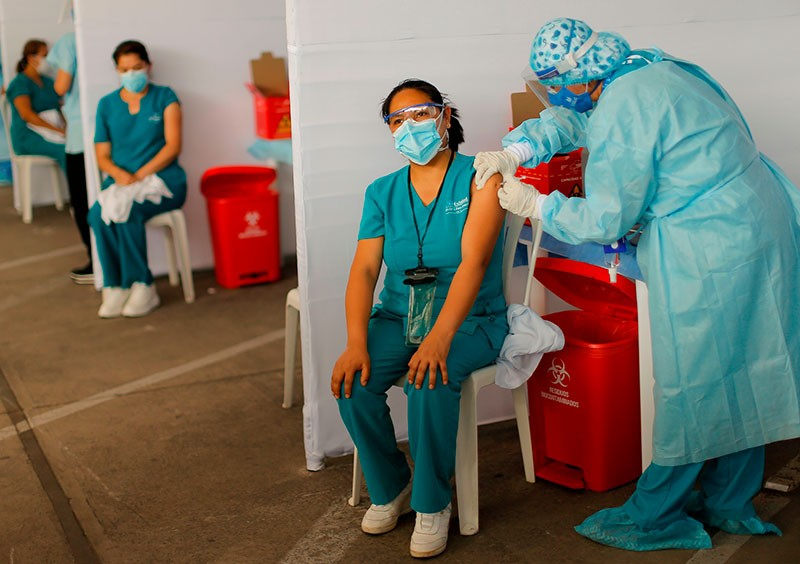 A health worker in protective gear administers a vaccine to another wearing scrubs, a mask and goggles.