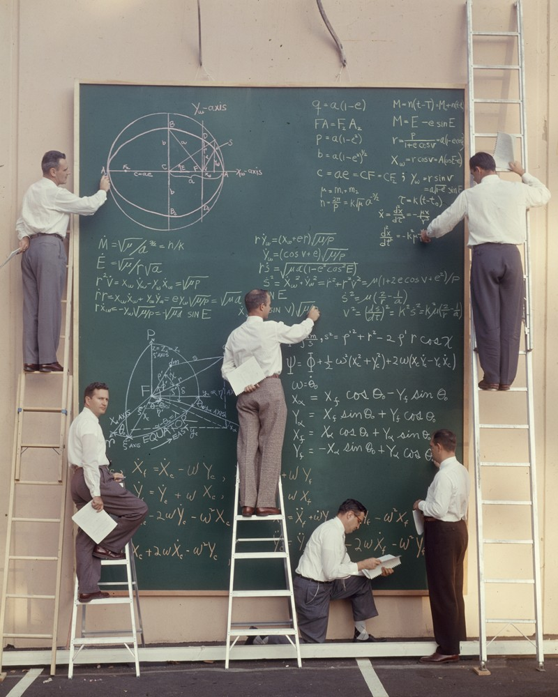 Six scientists on ladders write equations on a large chalk board.