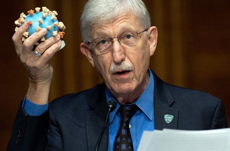 Francis Collins holds up a model of the virus SARS-CoV-2.