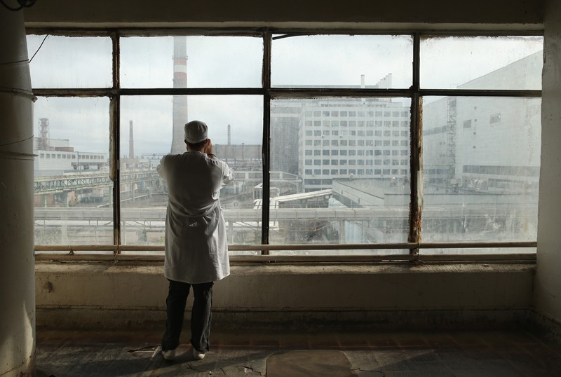 A visitor takes a photo through a window of the defunct Chernobyl nuclear facilities