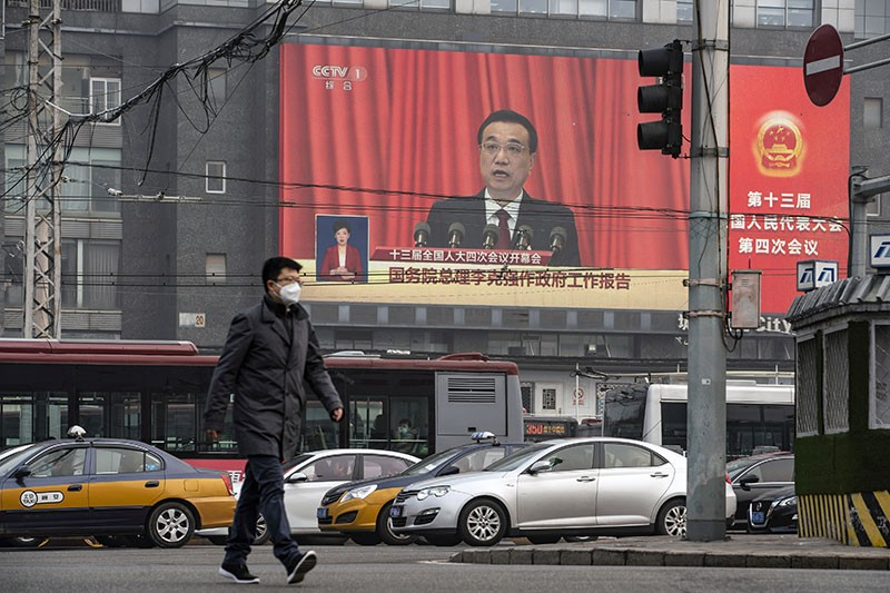 A man walks past a screen showing Chinese premier Li Keqiang speaking at the National People's Congress in Beijing.
