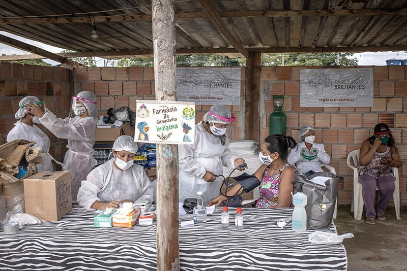Indigenous healthcare workers wearing PPE treat patients for the coronavirus in Manaus, Brazil