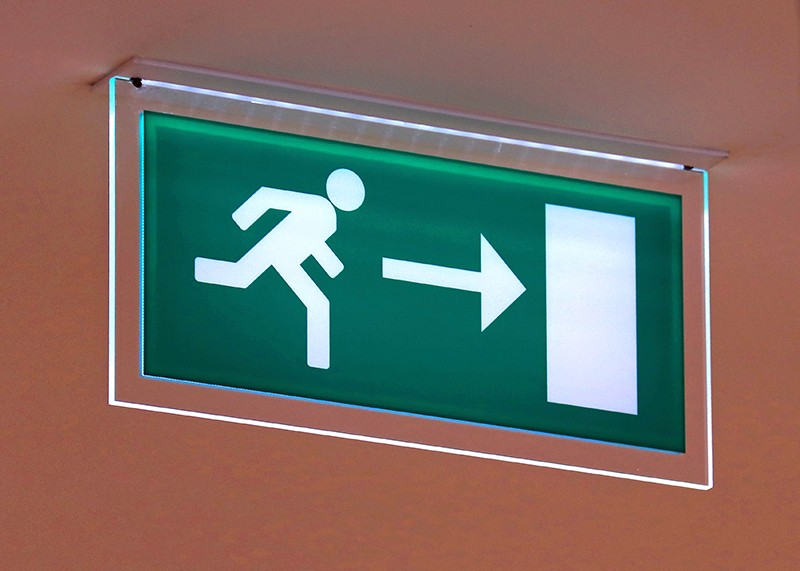 A green exit sign showing a stick figure of a person running towards a door directed by an arrow symbol
