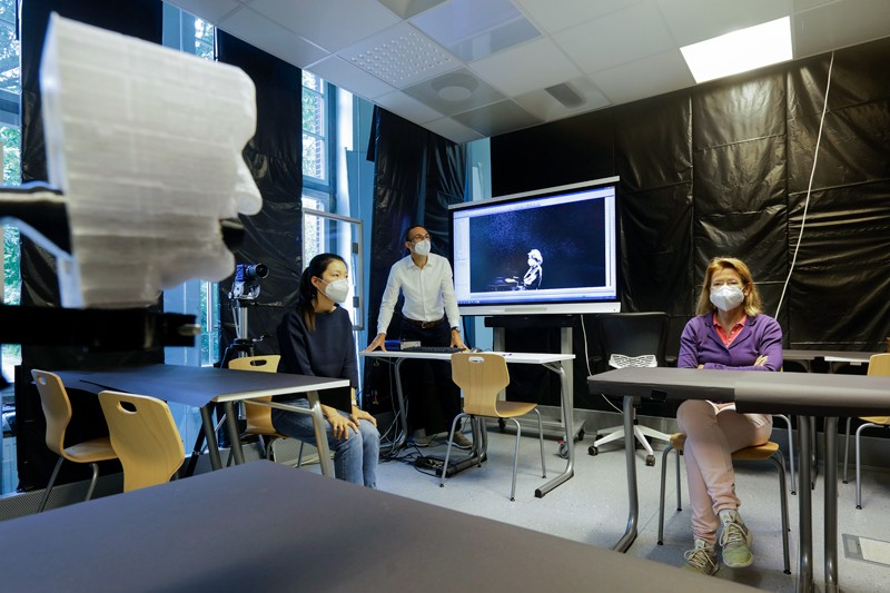 Three researchers in a room with desks and chairs with black sheeting on the walls and a mannequin head
