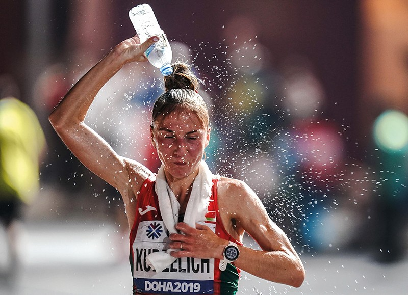 Athlete Sviatlana Kudzelich pours water over her head while running