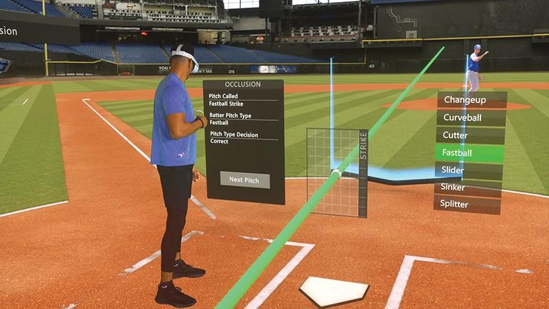 A man stands on a virtual baseball pitch