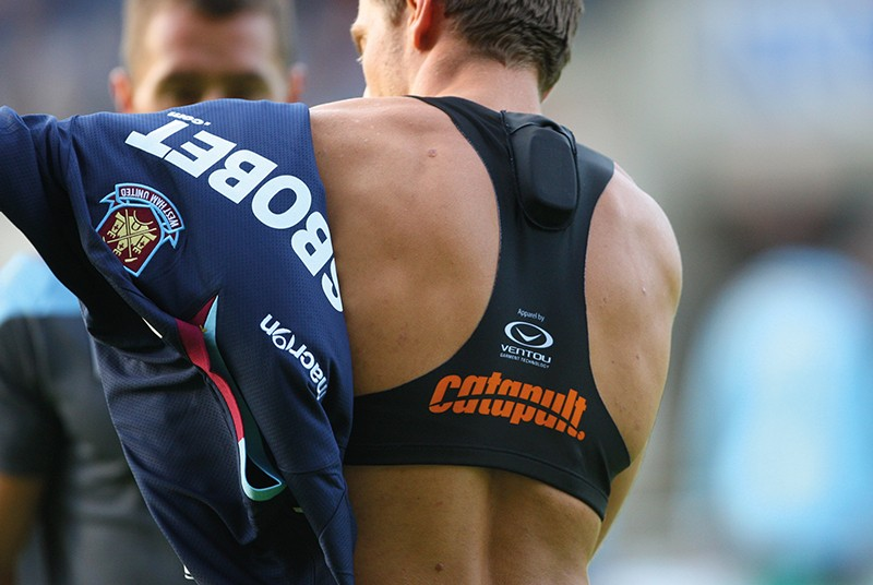 A male football player puts on a jersey over a vest containing a GPS sensor