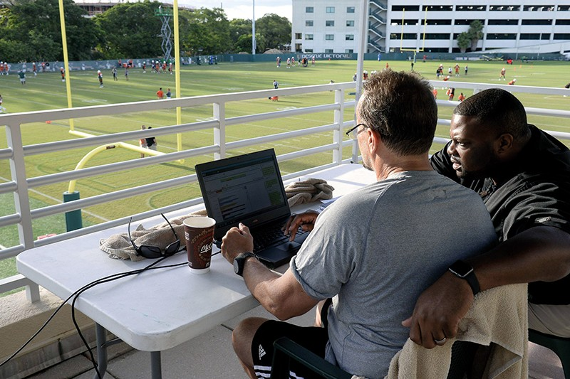 A coach and data analyst sit in front of a laptop overlooking a football pitch
