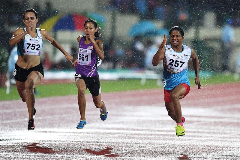Three athletes sprint in the rain on an athletics track