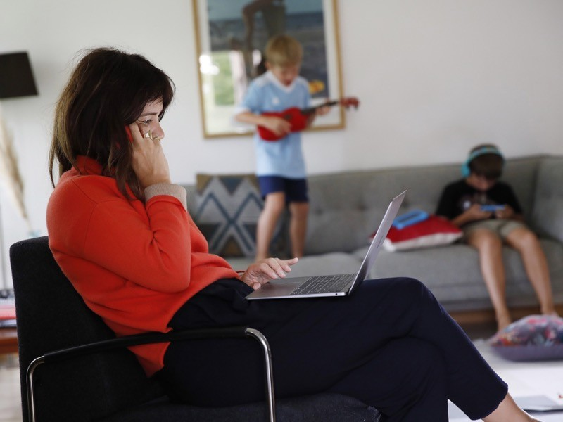 A woman works at a laptop computer in a lounge as children play beyond.