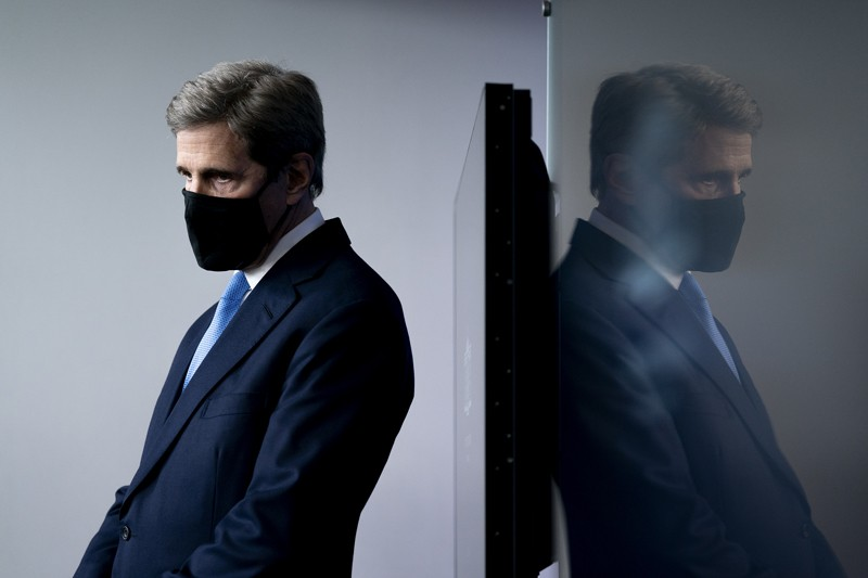 John Kerry wearing a protective mask during a news conference