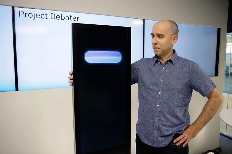 Noam Slonim stands with the IBM Project Debater