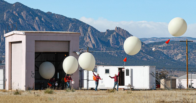 Series of superimposed pictures of a person releasing a large white balloon, with mountains in the background.