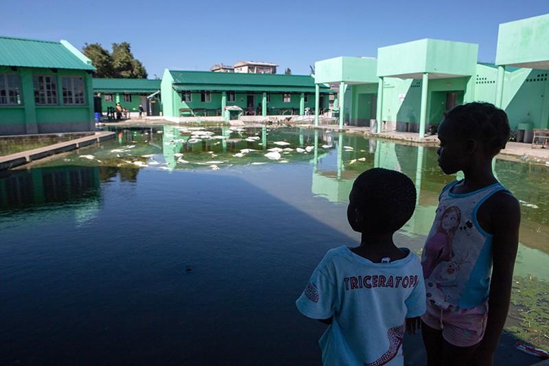 Children look at an elementary school's waterlogged playground in Beira, Mozambique