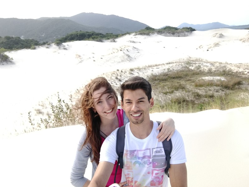 Two people standing among sand dunes, smiling at the camera.