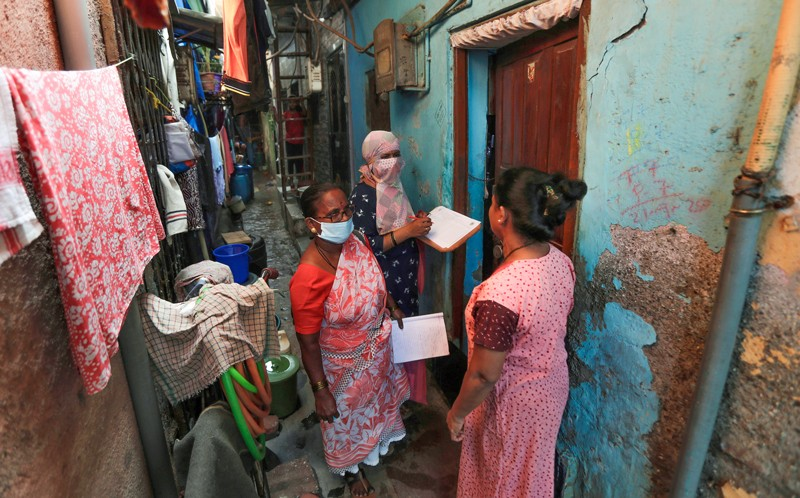 Two female health workers wearing face coverings and holding clip boards talk to a women in a narrow alleyway in India