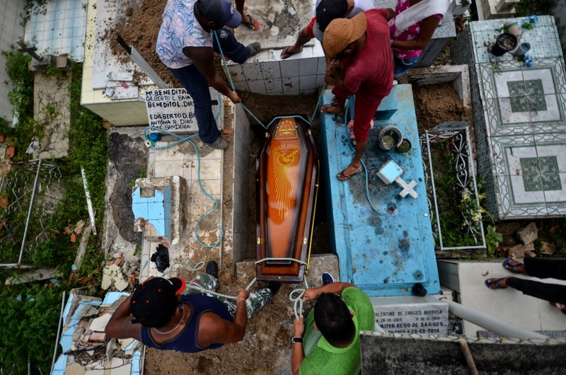 Gravediggers lower a coffin into a grave in a cemetery in Brazil