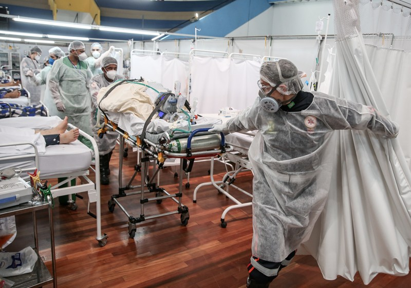 Medical staff members transport a patient on a stretcher at a field hospital in Brazil