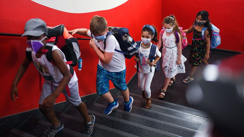 Students with face masks go upstairs to their classrooms at the Petri primary school in Dortmund, Germany.