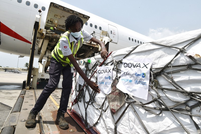 A worker adds a Covax sticker to a large shipment of Covid-19 vaccines unloaded from a plane in Ivory Coast