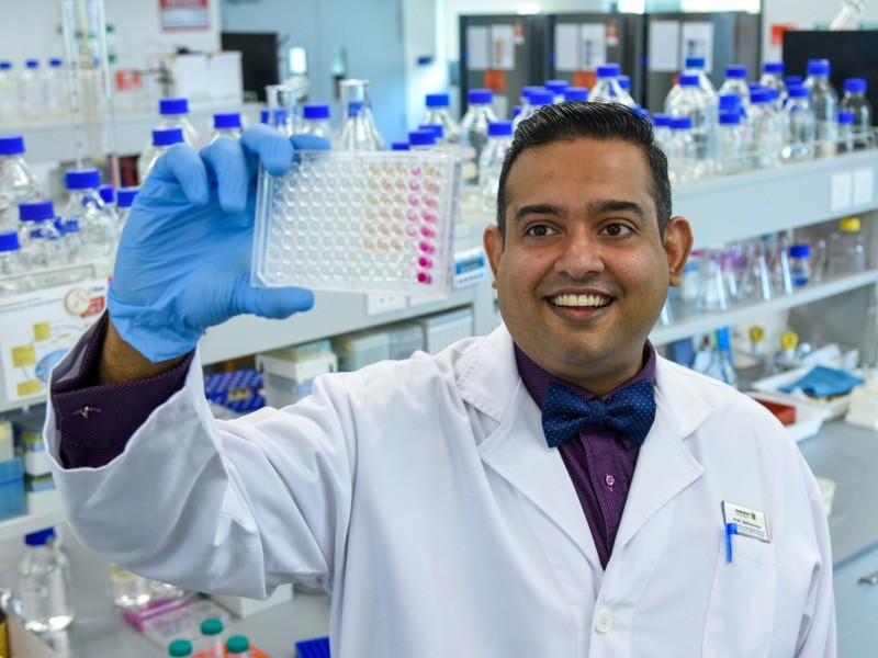 Prof Abhi holding a microplate with biological samples for analysis in his research laboratory.