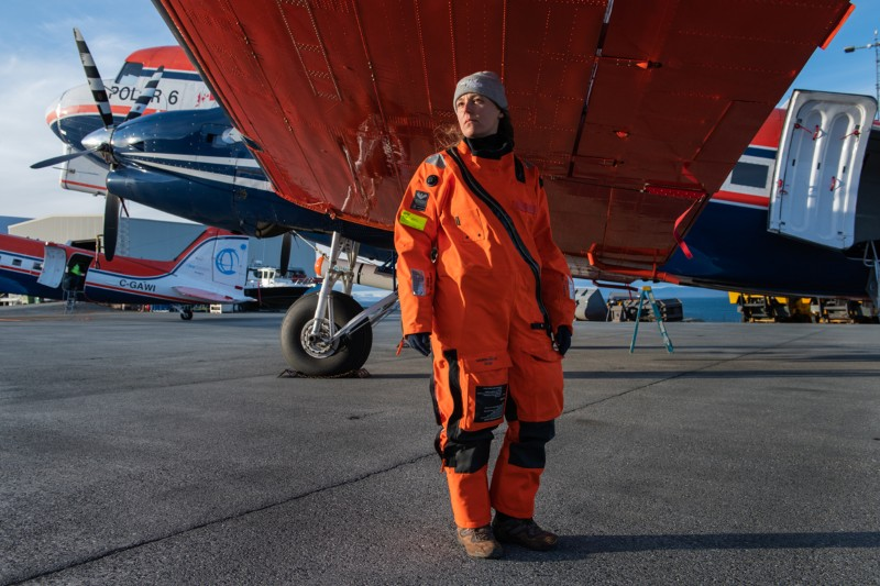 Cristina Sans Coll wearing an orange jumpsuit poses for a portrait beneath the wing of a plane
