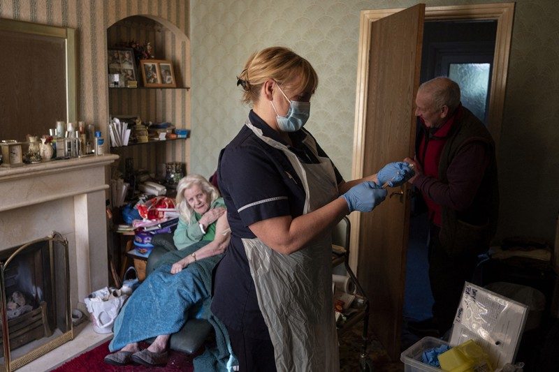 A healthcare worker prepares an Oxford/Astra Zeneca vaccine for an elderly woman in her home in the UK