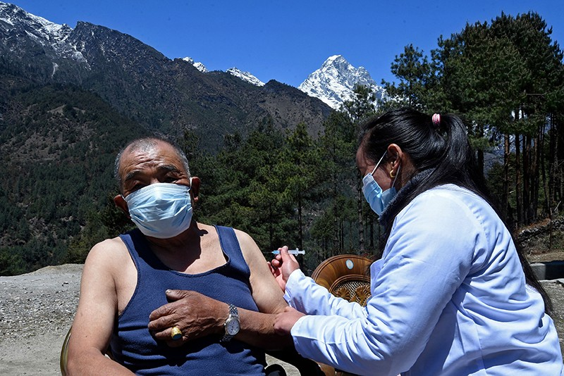 A health worker inoculates a man with a COVID-19 vaccine at a health post near Lukla
