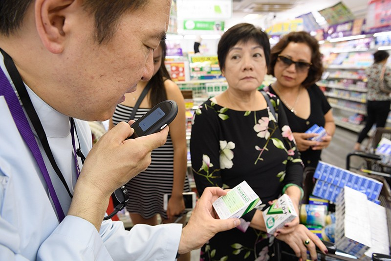 An employee uses a portable translation device to assist two customers in a shop in Tokyo, Japan