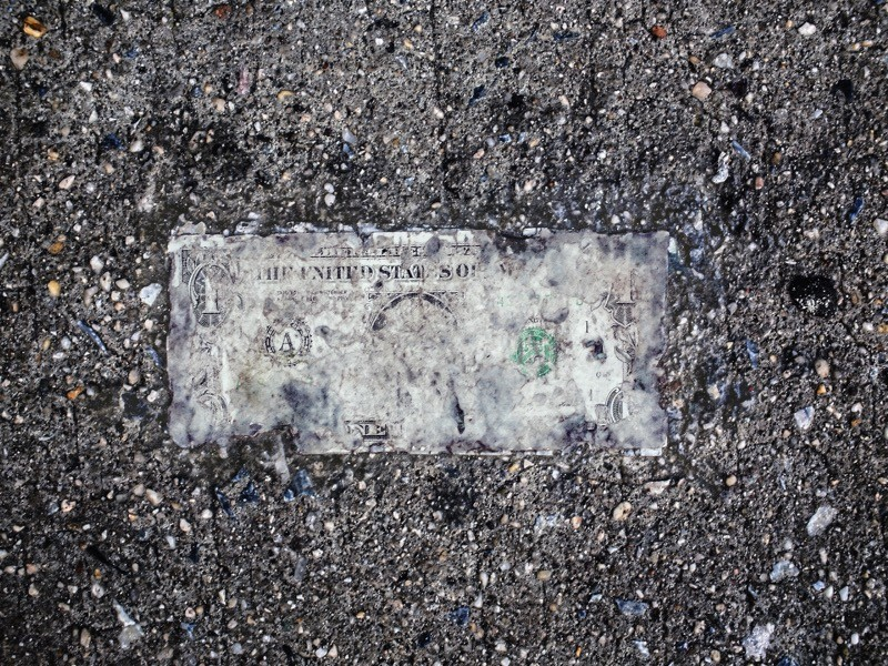 Still life of deteriorating one dollar bill on wet pavement.