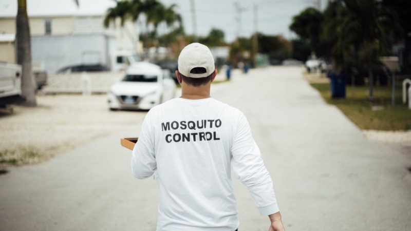 A man walks down a road in Florida holding a tray and wearing a shirt that reads 'Mosquito Control' on the back