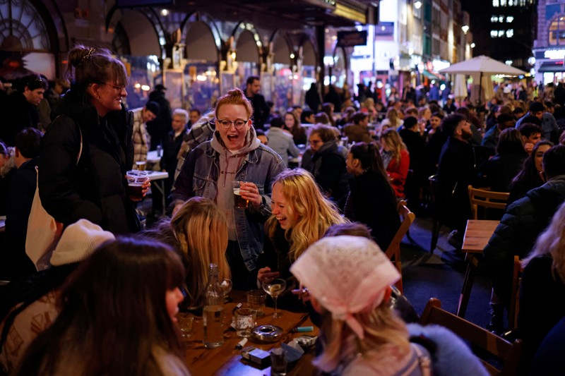 large numbers of people in coats sitting at outside tables, drinking.