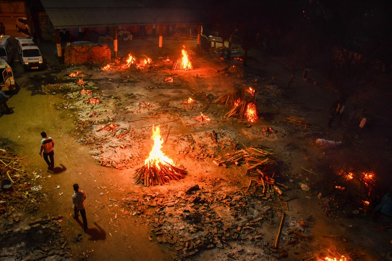 Multiple funeral pyres, seen from above at night.