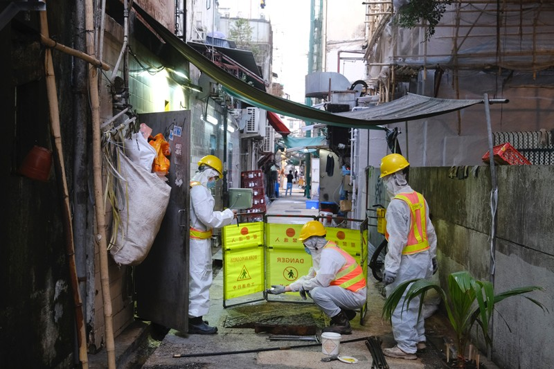 Technicians and government investigators wearing PPE collect samples from a sewage in Hong Kong