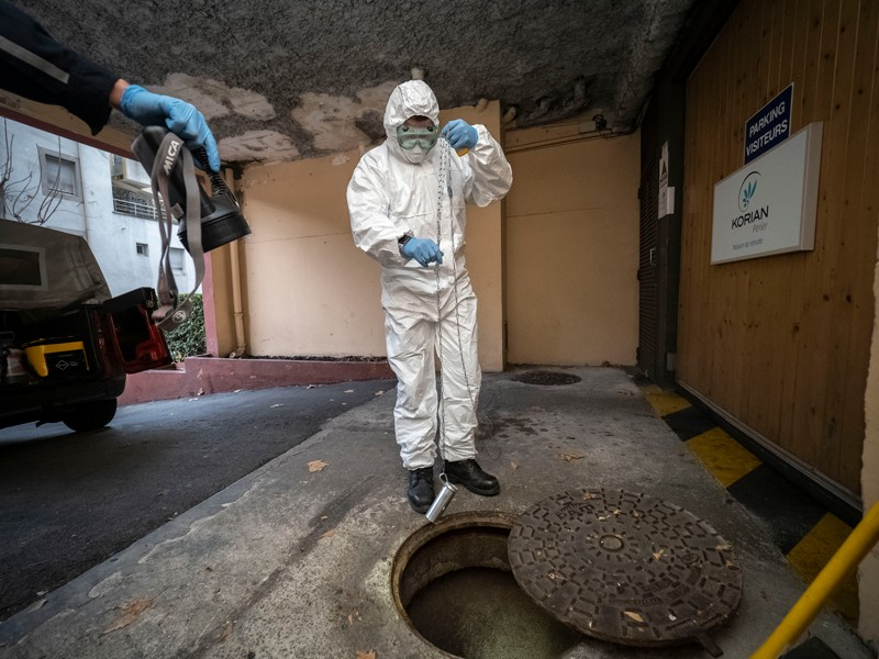 A firefighter wearing a protective suit takes samples from Marseille sewage water